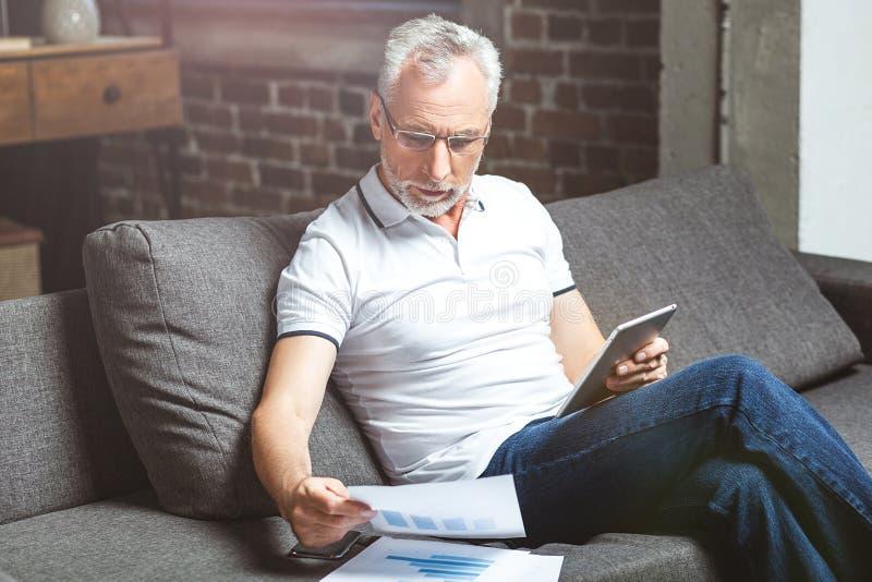 人戴着眼镜使用在数字片剂 免版税库存图片