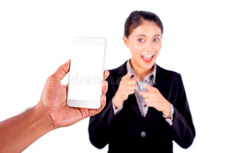 人手举行拍指向电话和微笑与立场亚裔美丽的女商人的照片的手机 免版税库存照片