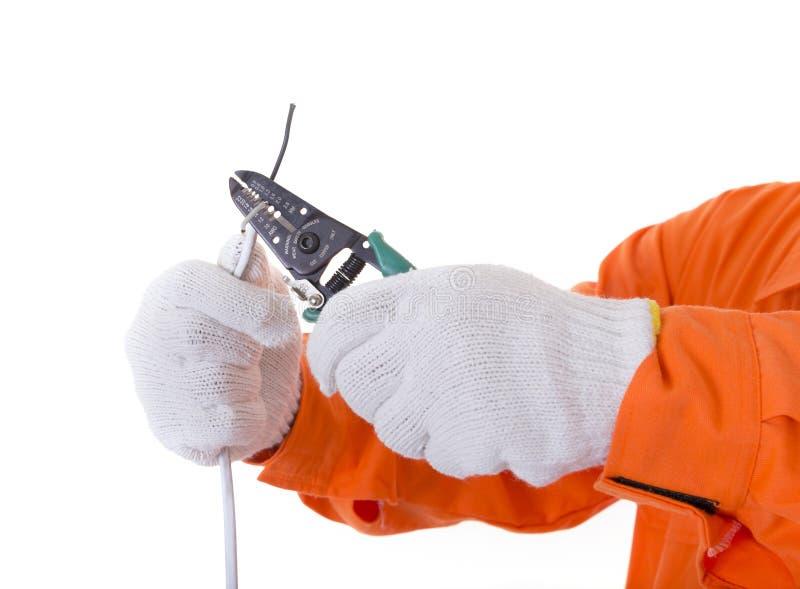 人手准备好举行的切削刀切开电线或缆绳 Isol 免版税图库摄影