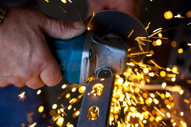 人手切开金属棒使用与飞行的火花的电研磨机  免版税库存照片