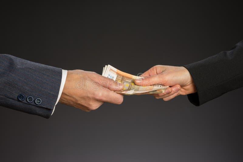 人手和五十欧元钞票,被隔绝的灰色背景 给金钱,贿款 钞票概念毁坏美元信包查出的白色 男人和妇女手 图库摄影
