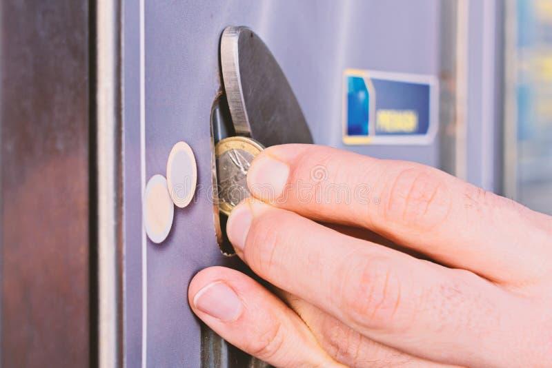 人手指放一枚欧洲硬币入一台自动分配器 免版税库存照片