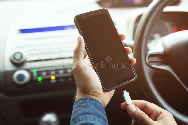 人手藏品充电在汽车的电池流动智能手机 图库摄影