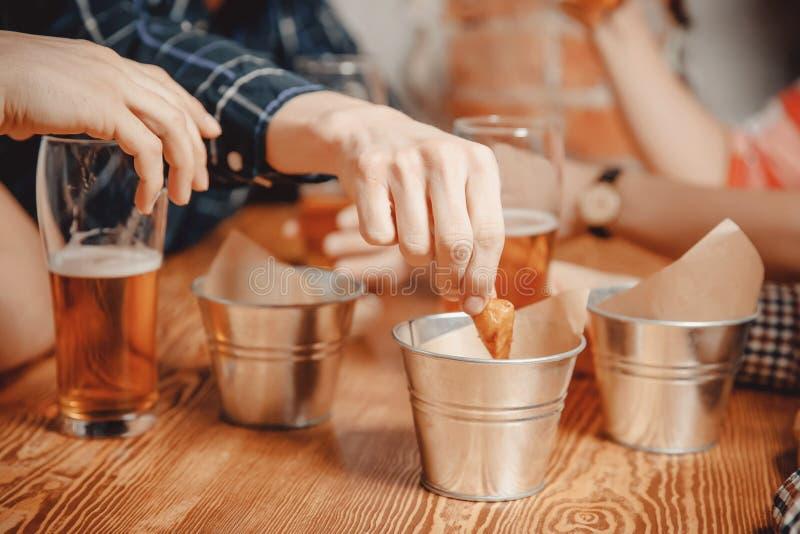 人手采取快餐薄脆饼干、油煎方型小面包片用调味汁和饮料啤酒在客栈酒吧在木桌上 免版税库存照片