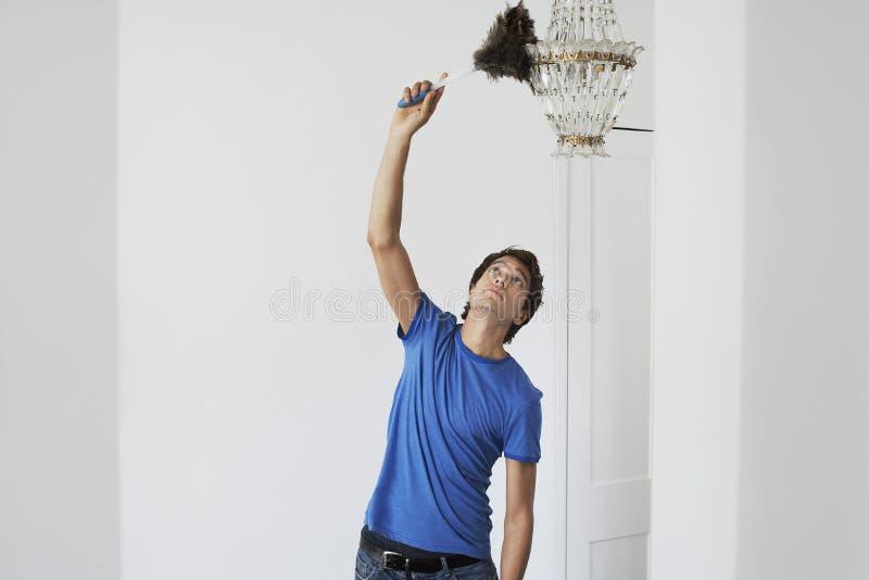 人打扫灰尘水晶枝形吊灯在家 免版税图库摄影