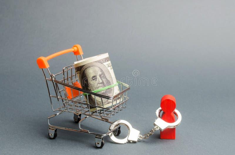 人扣上手铐对捆绑在超级市场推车的金钱 人由大债务或责任的负担限制 库存照片