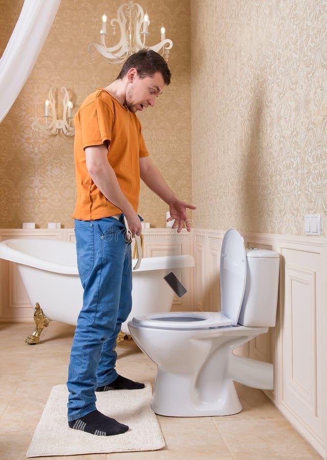 人投下在洗手间的手机 免版税库存图片