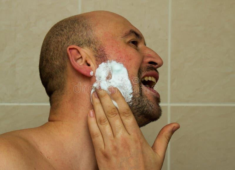 人投入了刮脸泡沫,胶凝体,在刮他的与剃须刀前的他面孔 人护肤概念 免版税库存照片