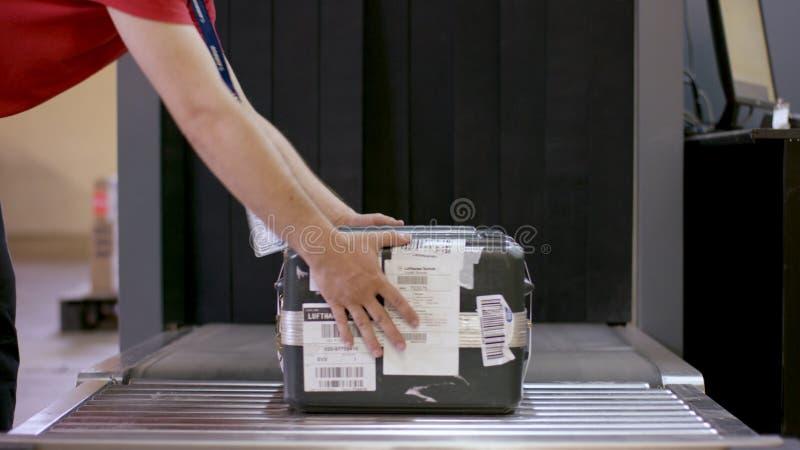 人投入了行李在登记处柜台在机场 在机场登记处柜台的X光机 手安全检查  库存图片