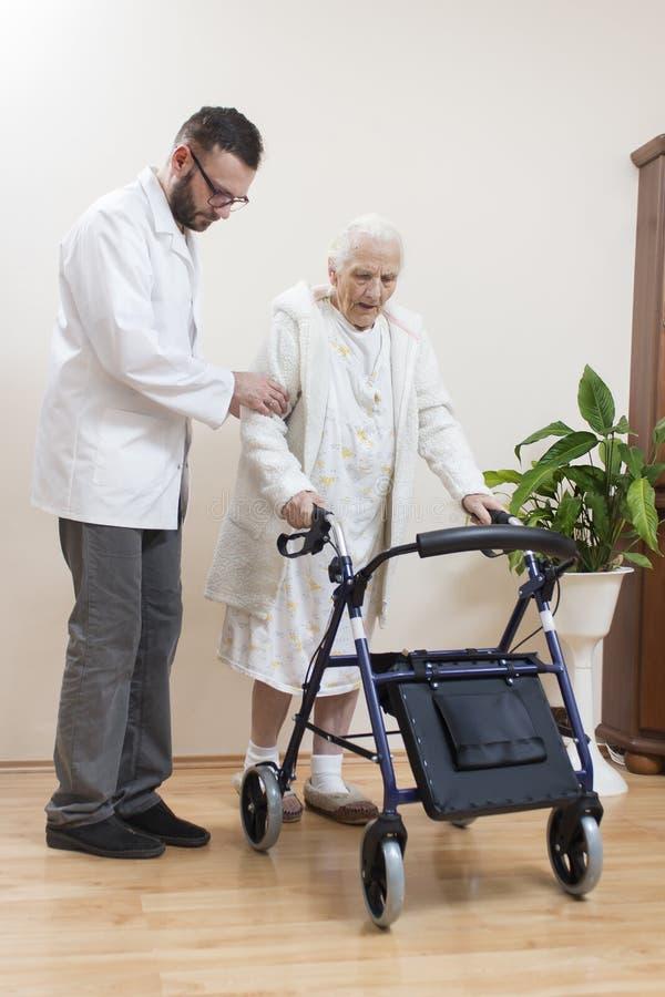 人护士帮助一个非常老妇人在修复步行者帮助下走 免版税库存图片