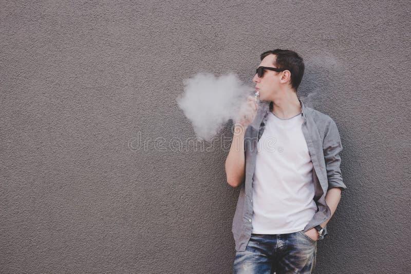 年轻人抽烟的, vaping的电子香烟或vape 灰色背景 库存照片