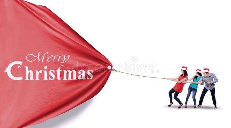 人拉扯圣诞节横幅 免版税库存照片