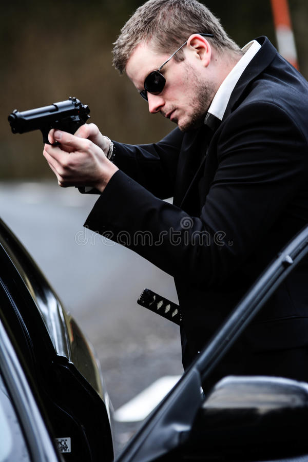 人拉扯在汽车的一杆枪 免版税库存照片