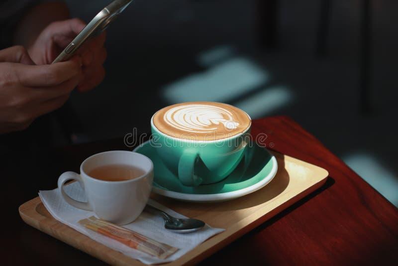 人拍了与智能手机的照片 与郁金香foa的热的咖啡拿铁 库存图片