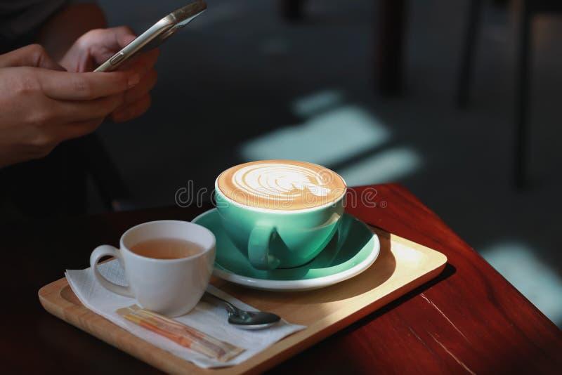 人拍了与智能手机的照片 与郁金香foa的热的咖啡拿铁 库存照片