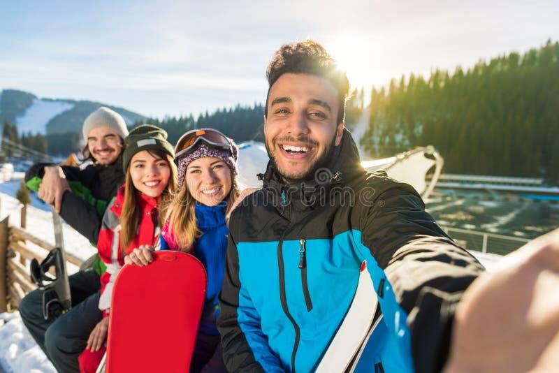 人拍Selfie照片的滑雪雪板手段冬天雪山愉快的微笑的朋友 免版税库存照片