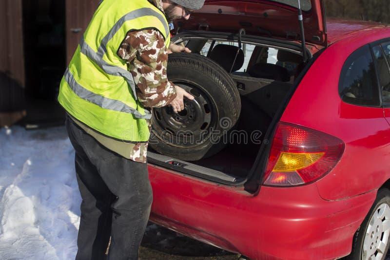 人拔出从穿一件反射性背心的汽车的后车箱的一个备用轮胎 免版税库存图片