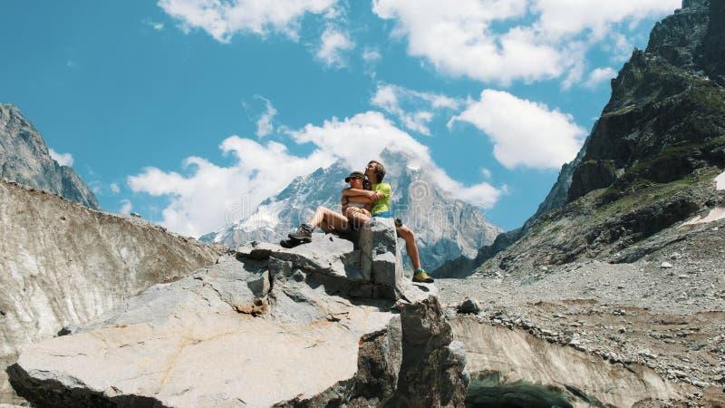 人拥抱一次行军的一名妇女,在爱 家庭游人已婚夫妇坐岩石并且享用山 库存图片