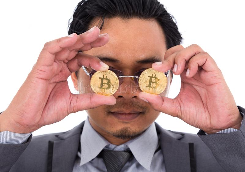 人拿着在白色隔绝的他的眼睛前面的一硬币bitcoin 图库摄影