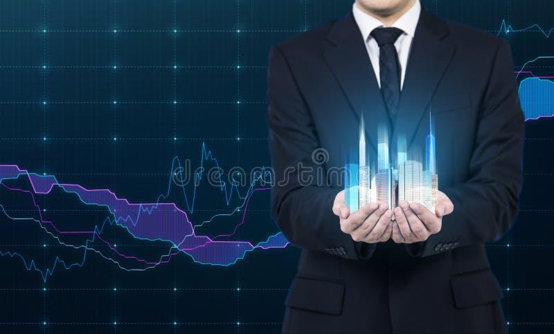 人拿着摩天大楼全息图作为财政成功的标志 图库摄影