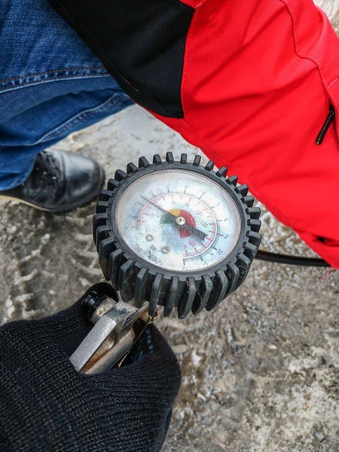 人拿着有的一个气泵膨胀的车胎一个压力表 免版税图库摄影