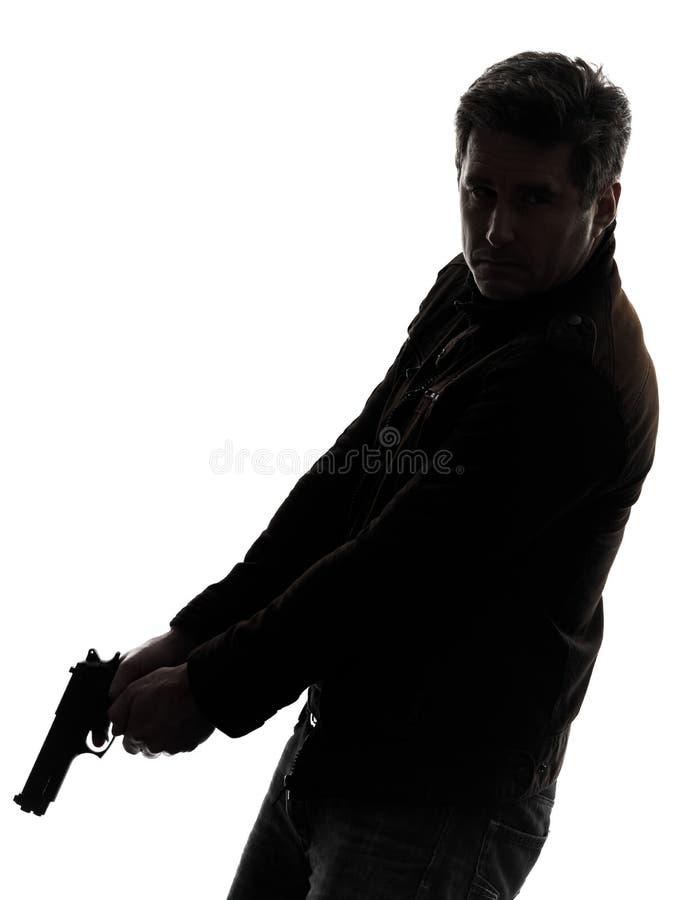 人拿着枪走的剪影的凶手警察 免版税库存照片