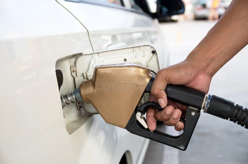 人拿着燃料喷嘴增加在汽车的燃料在加油站 库存图片