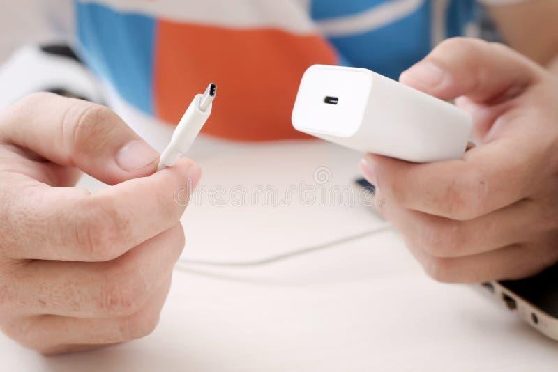 人拿着的适配器和手中USB的缆绳 库存照片