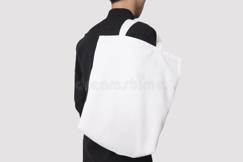 人拿着袋子大模型空白模板的帆布织品 免版税库存照片