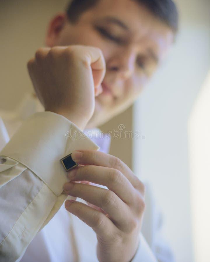 人按在袖子的链扣 免版税库存图片