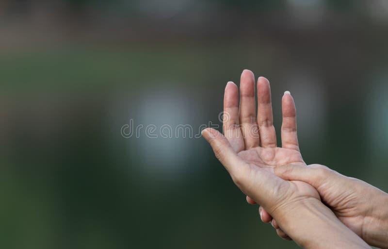 人按摩的特写镜头手她的从痛苦的手在自然背景的健康概念 免版税库存照片