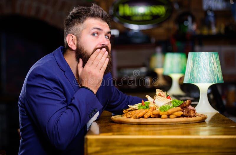 人接受了与油煎的土豆的膳食炸鱼排肉 可口膳食 享受膳食 高卡路里快餐 欺诈膳食概念 免版税库存照片