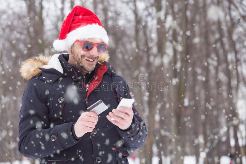 人接近的画象有在网上支付与他的c的圣诞老人帽子的 免版税库存图片