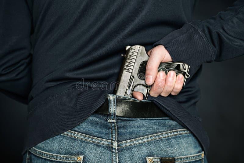 人掩藏一把手枪在牛仔布传送带下 免版税库存图片