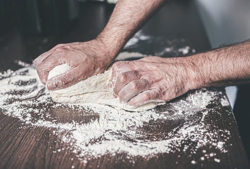 人揉的发酵面团的手在被撒粉于的厨台的 图库摄影