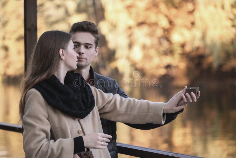 人提出一个提案给女孩 一对年轻爱恋的夫妇在有黄色树的秋天公园站立 r 免版税库存图片