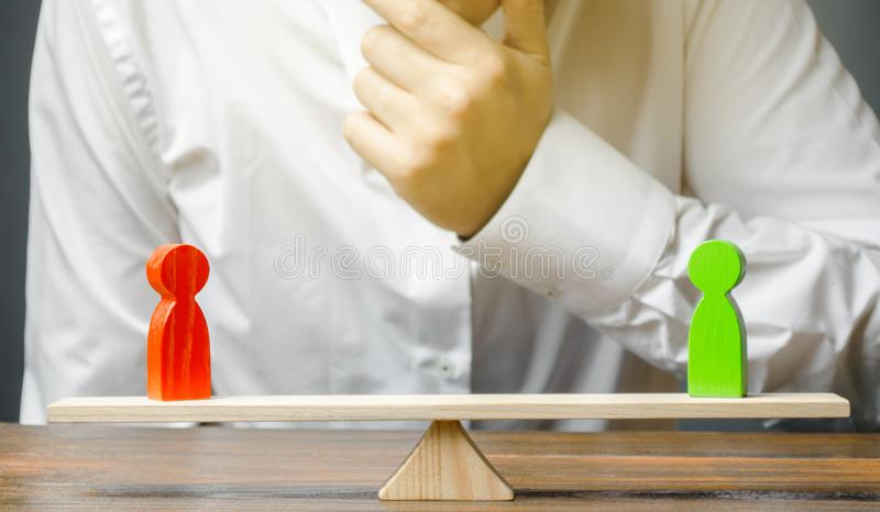 人握他的在下巴神色的手在的敌手红色和绿色图标度 被衡量的决定 解决冲突 免版税库存图片