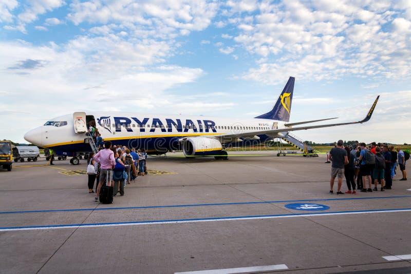 人搭乘瑞安航空公司爱尔兰便宜的航空公司飞机波音737有多云天空背景 免版税库存照片