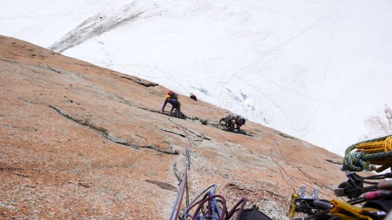 人攀岩一条陡峭的垂直的花岗岩攀岩路线在勃朗峰附近的法国阿尔卑斯在白雪冰川上 免版税图库摄影