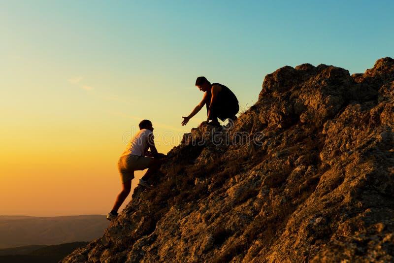 人攀岩与另一人帮助 免版税图库摄影
