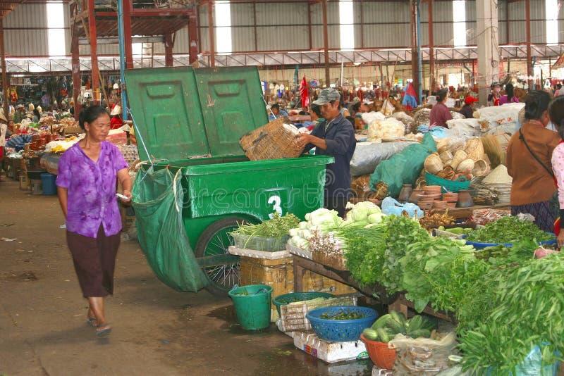 人收集垃圾在菜市场上,老挝 免版税库存图片