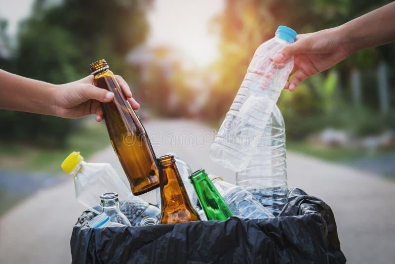 人放入的手拿着垃圾瓶塑料的和玻璃回收袋子 库存图片