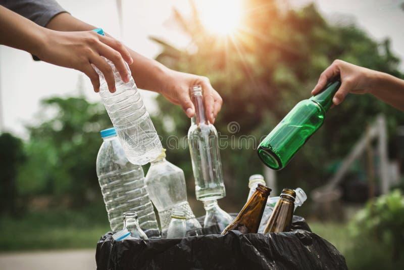 人放入的手拿着垃圾瓶塑料的和玻璃回收袋子 图库摄影
