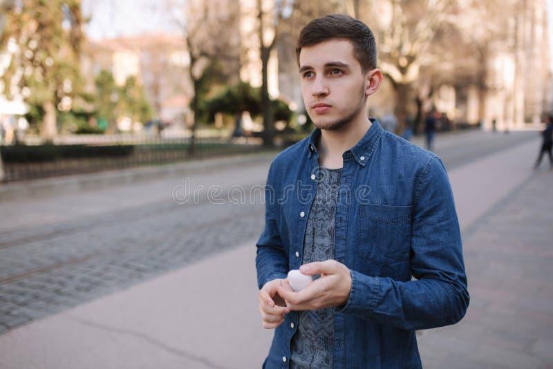 人放在适当的位置他的无线耳机 蓝色衬衣立场的帅哥在中心,如果城市 库存图片