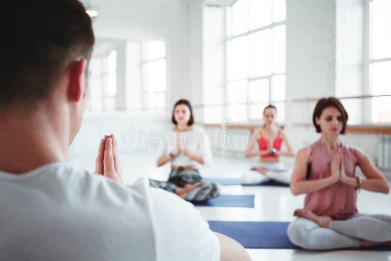 人教练训练小组女子维护的医疗保健的瑜伽锻炼在白色类 一起人practis瑜伽姿势 库存照片