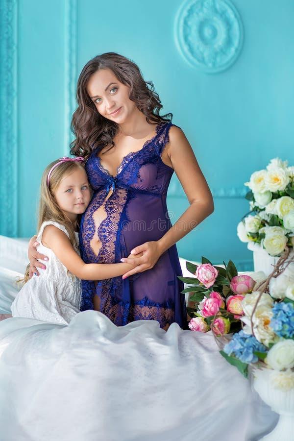 令人敬畏的性感的紫色礼服的Beautifull年轻深色的孕妇接近蓝色沙发和逗人喜爱的花与女儿一起 库存照片