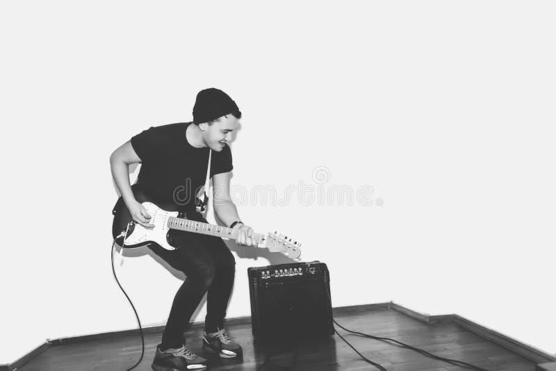 令人敬畏的疯狂的时尚年轻音乐家岩石吉他演奏员跳充满激情在演播室 时髦的岩石情感人 投反对票 免版税图库摄影