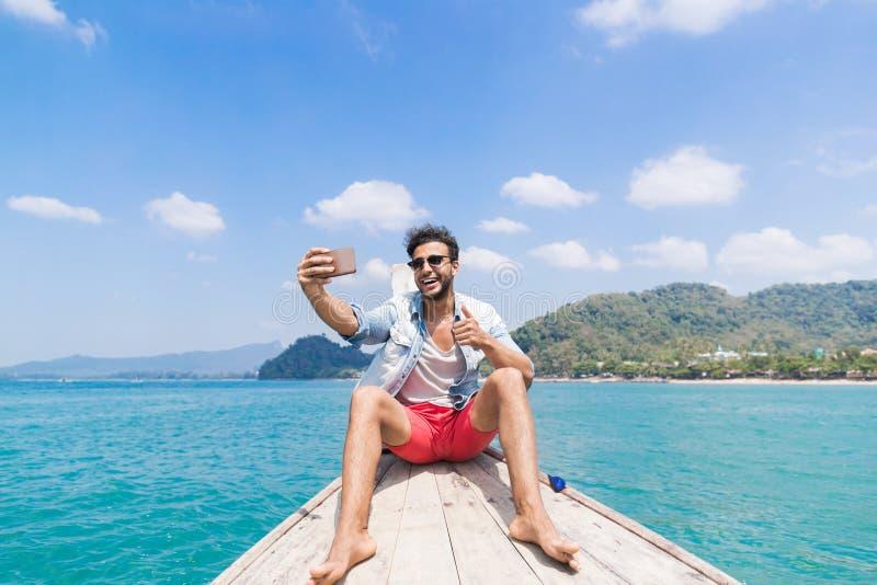 年轻人旅游风帆长尾巴泰国小船讲话拍在细胞巧妙的电话的Selfie照片 图库摄影