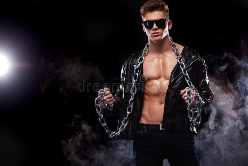 人时尚 一个残酷和适合人的特写镜头画象露胸部在有链子的一皮夹克 运动员爱好健美者 免版税库存图片