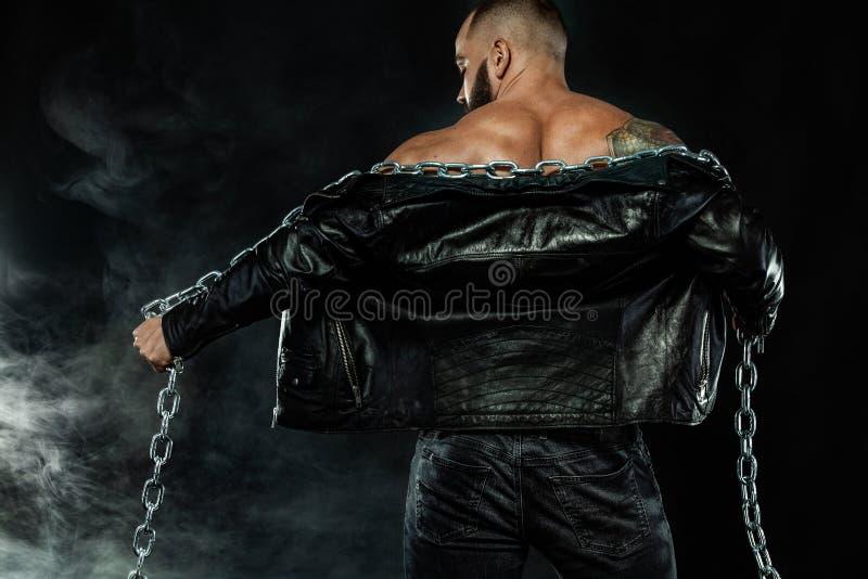 人时尚 一个残酷有胡子的人的特写镜头画象露胸部在有链子的一皮夹克 运动员爱好健美者 图库摄影